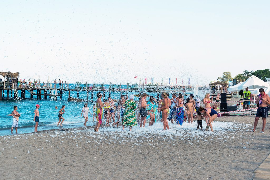 Kemer, Turkey-August 21, 2014. Foam Party on resort. Group of people enjoying in drinking, dancing and music.