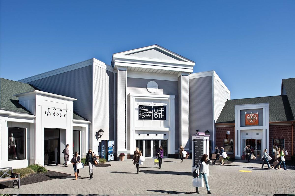 Woodbury Commons Outlet Stores on a sunny day in New York So why would you go to the Woodbury Outlet Mall NY, when downtown New York also has many stores to offer with perhaps the same discounts? The answer is easy.